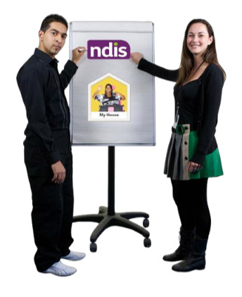 Two friendly looking presenters standing near an information board which had info about the NDIS and group homes on it.